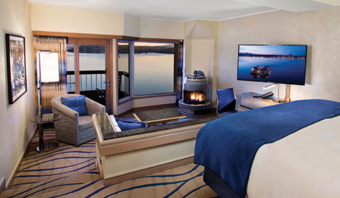 room with a lake view and fireplace