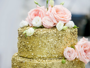 Beautiful three-story golden wedding cake decorated with flowers