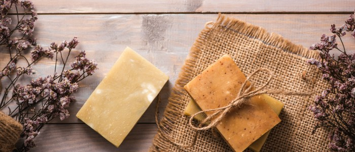 Natural soap with dried flowers on wooden background.