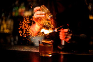Professional bartender adding to a cocktail brown spice and flame it